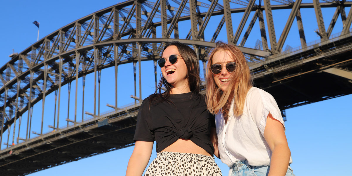 Two girls standing in front of a large bridge