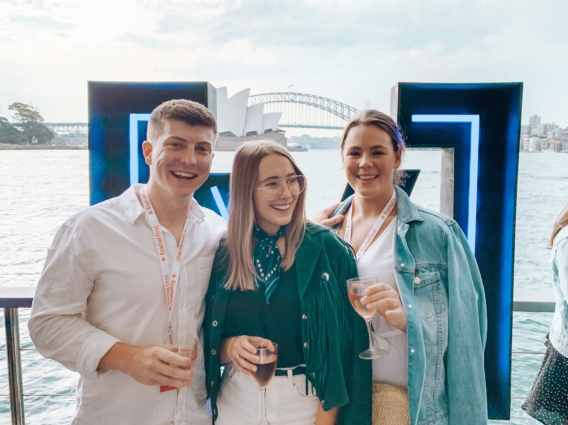 Three people standing in front of a large V letter on a boat