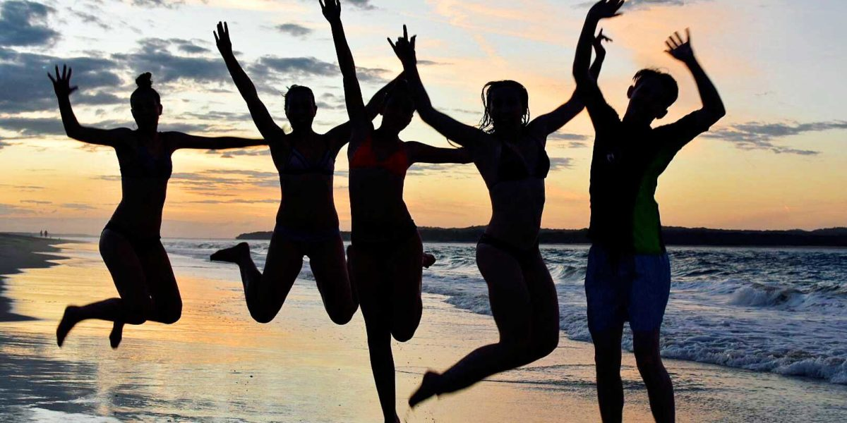 5 teenagers jumping on the beach at sunrise