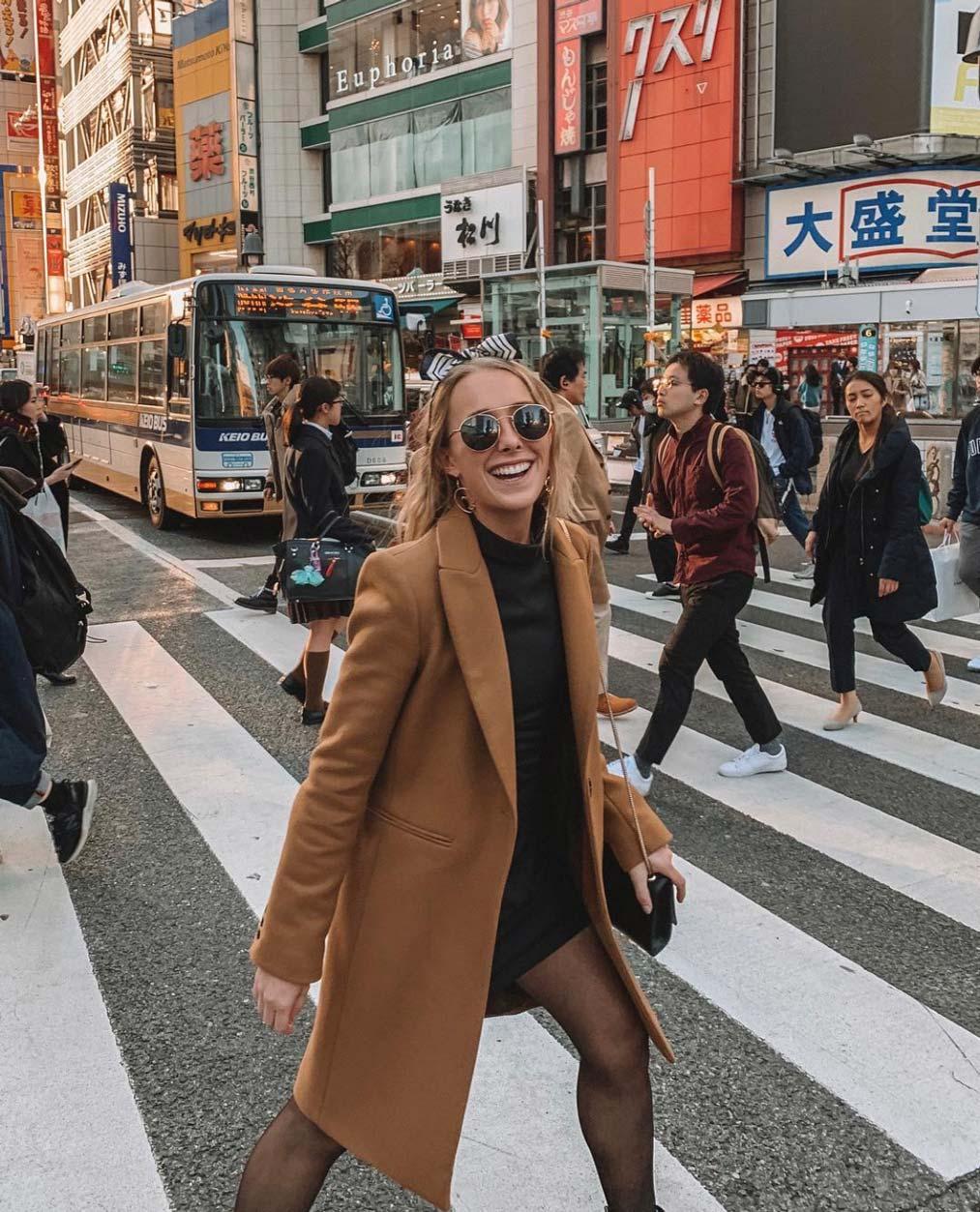A girl in a brown coat walking across a busy cross walk