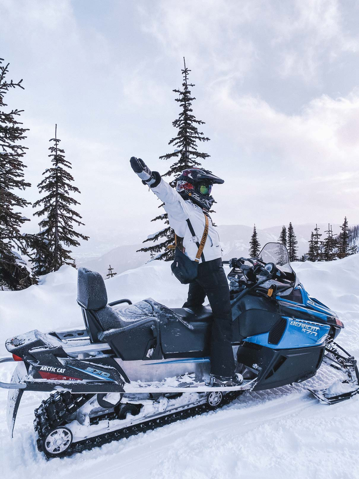 Girl standing on top of a snow mobile in a field of snow